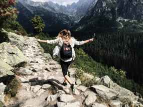 woman walking on rock path at side mountain with arms extended.