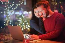 woman leaning man, both smiling while on the computer