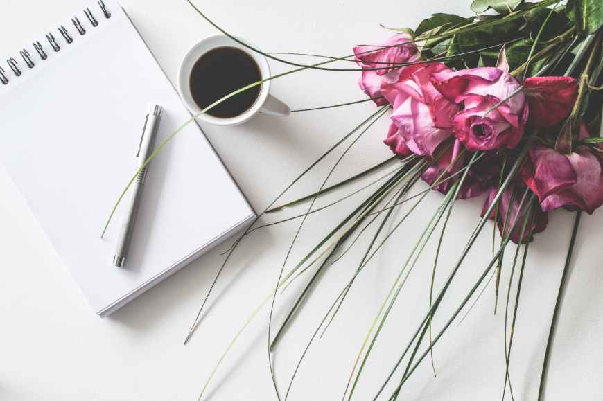Note pad, cup of coffee and pink flowers bouquet