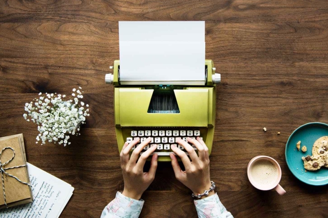 person using green typewriter on brown wooden